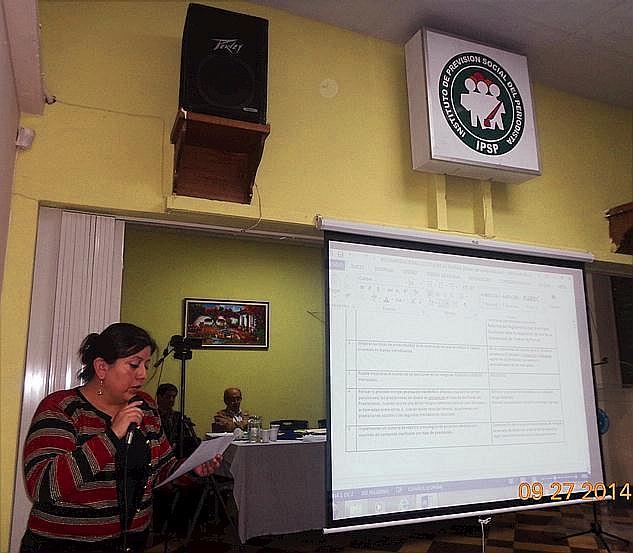 Lucía Dubón López, presidenta del Consejo Directivo del IPSP, leyendo uno de los a+rtículos de reglamento cuyo contenido es proyectado a los asambleístas en la pantalla retráctil (Foto, por Julio Trejo Pineda).